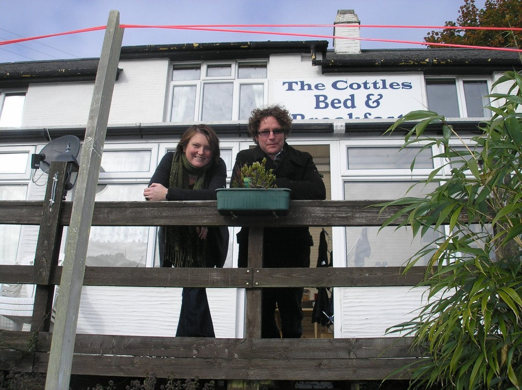 The owners and hosts of The Cottles, Jo and Mark, standing on the decking at the rear of the building and smiling to camera.