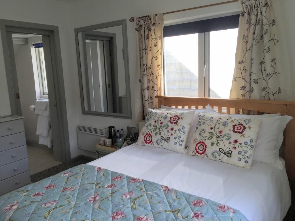 A bright double bedroom showing the door to an en suite shower room.