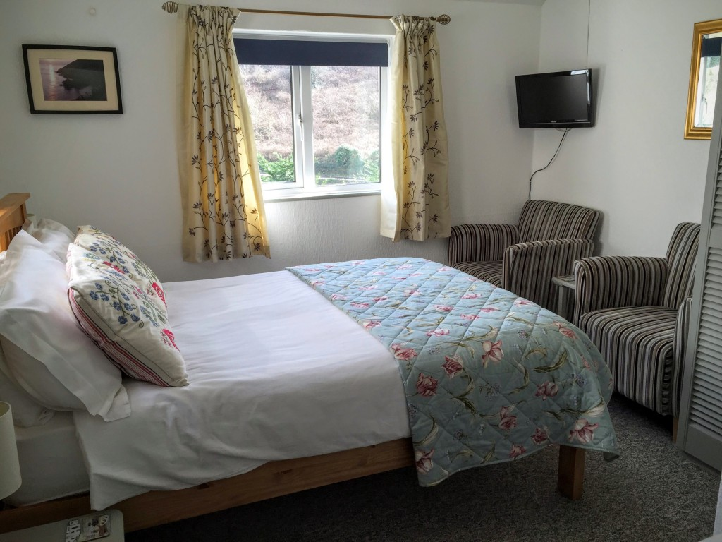 A bright double bedroom with TV and upholstered armchairs.