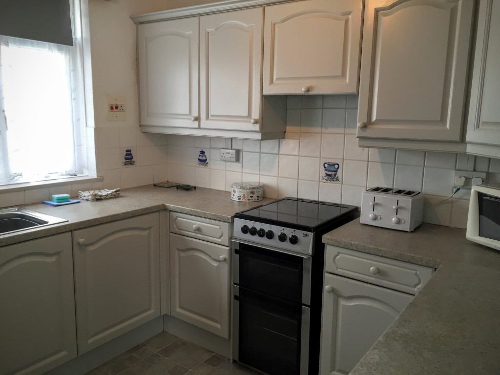 A clean and tidy kitchen area with hob and oven, toaster, and microwave.