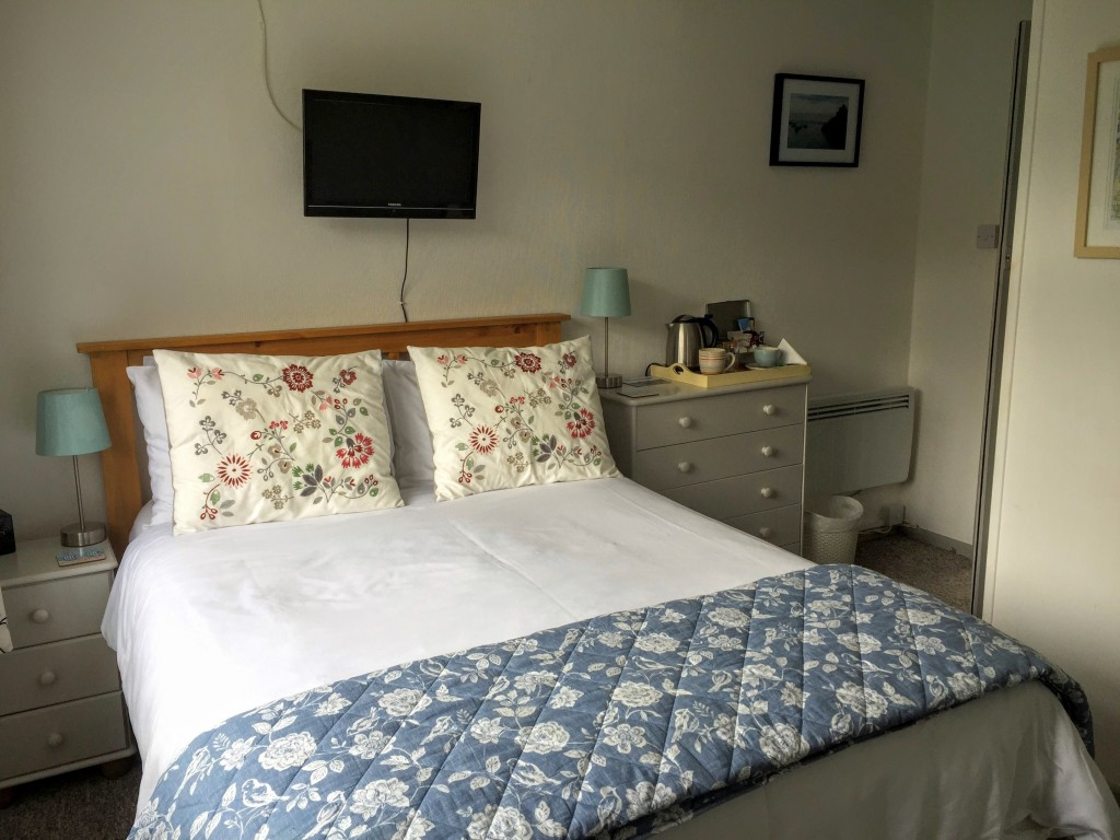 A bright double bedroom with TV and bedside chests of drawers.