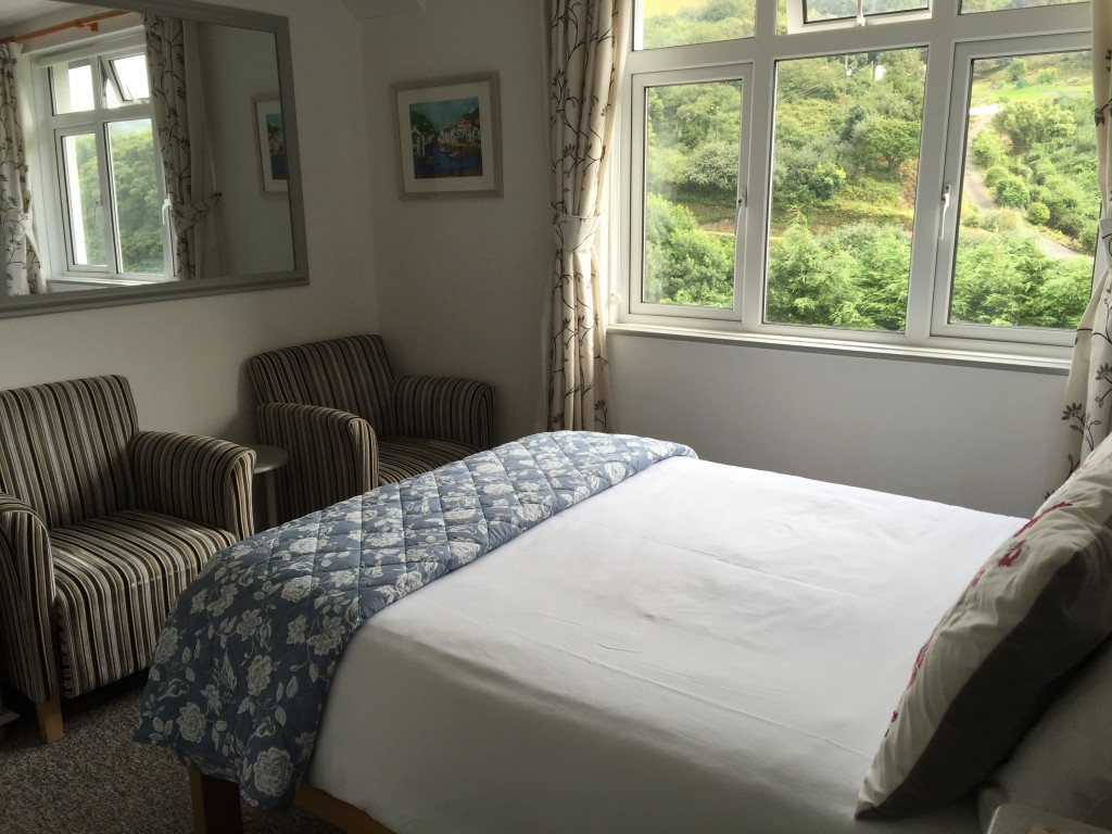 A bright double bedroom with upholstered armchairs, overlooking the valley outside.