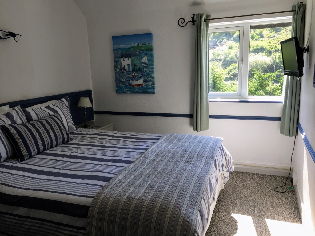 A kingsize bedroom with TV and views of Polperro valley.