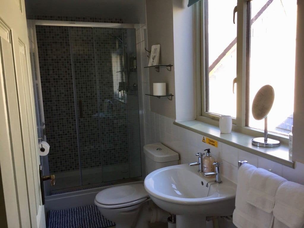 A tiled en suite bathroom with large shower and white towels.