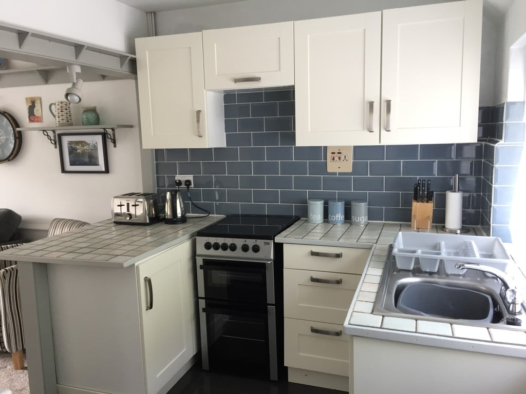 A tiled kitchen area with oven and hob, toaster, and kettle.